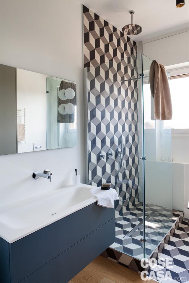 bagno, mobile sospeso con lavabo incassato, rubinetteria a parete, specchio, box doccia, rivestimento effetto 3D, soffione a soffitto, finestra