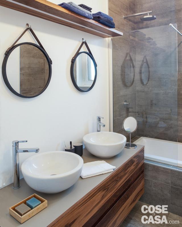 bagno, piano con due lavabi, rubinetti a colonna, specchi tondi, ripiano, vasca, divisorio vetrato, rivestimento in gres grigio