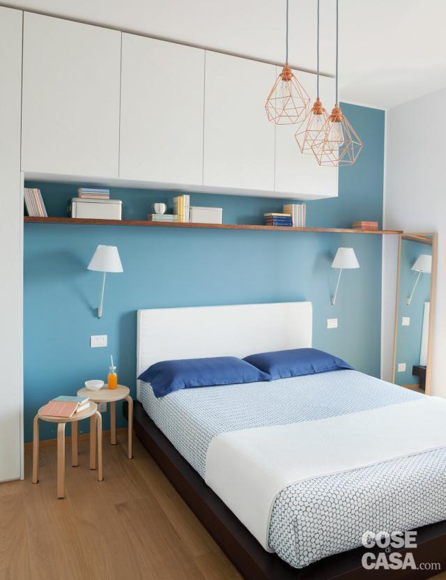camera, letto matrimoniale, armadio a ponte, parete azzurra, applique bianche, sospensioni  in finitura rame, armadio a ponte laccato bianco, specchio