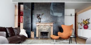 soggiorno con camino, divisorio in lamiera, poltrona di design arancione con poggiapiedi, mobile sospeso in laccato bianco, divano in pelle, controsoffitto