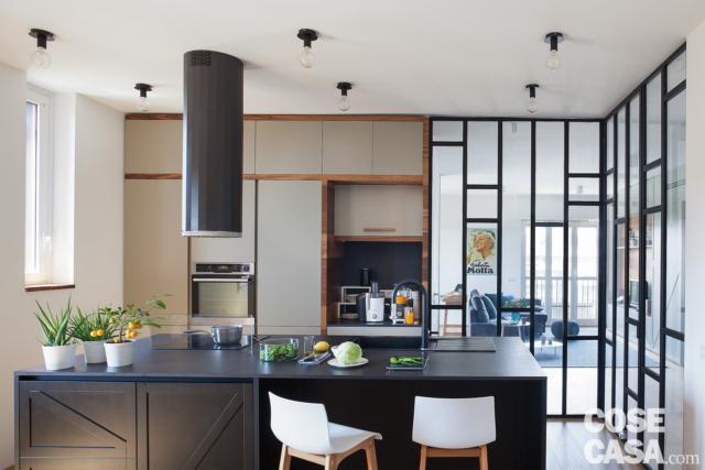 cucina con mobili che dividono, parete vetrata, isola centrale, cappa a cilindro, sgabelli, controsoffitto, faretti