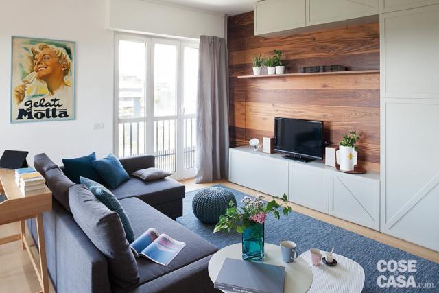 zona conversazione, divano con chaise-longue, tappeto, tavolino, parete attrezzata con boiserie, zona tv, portafinestra