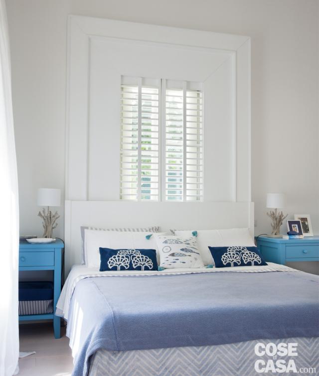 villa al mare, camera matrimoniale, letto, finestra, frangisole, comodini azzurri in legno, abat-jour, copriletto azzurro, cuscini