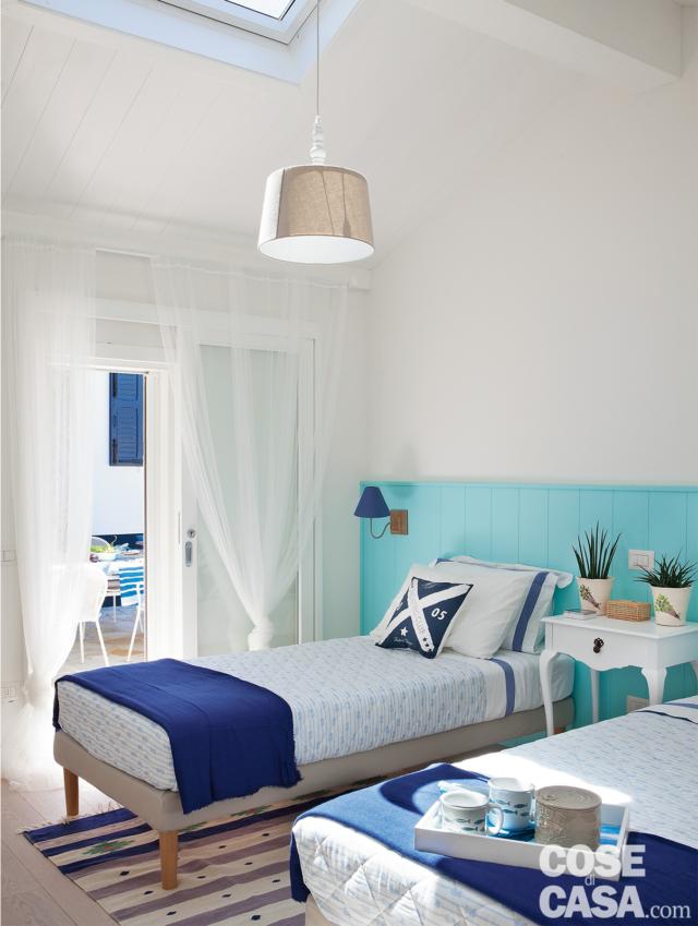 camera a due letti, lucernario, lampada a sospensione, letti singoli, boiserie azzurra, plaid blu, tappeto a righe