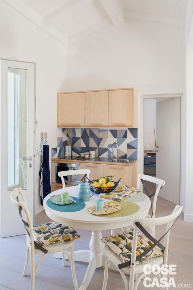 villa al mare, angolo cottura, mobili in legno di frassino, piastrelle decorate, tavolo da pranzo rotondo bianco, sedie bianche, portafinestra porta, pavimento in gres