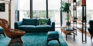 soggiorno, vetrata con tende a rullo, mobile divisorio passante, divano rivestito in tessuto color ottanio, pouf, tapeto, lampada d aterra, poltroncina in vimini, tavolino