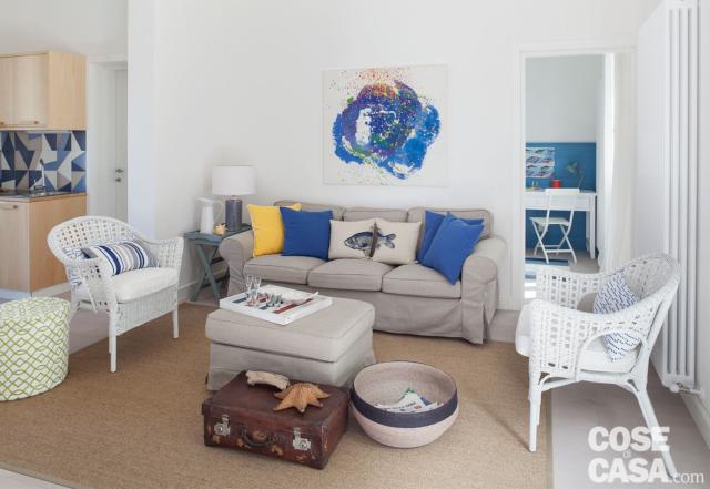 villa al mare, soggiorno, divano grigio, pouf, poltroncine in midollino bianco, tappeto écru, radiatore, baule, vaso