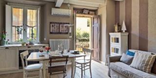 monolocale, ingresso, radiatore, finestra, zona cottura, travi a vista, tavolo e sedie shabby chic, pavimento in legno, divano, cassettiera