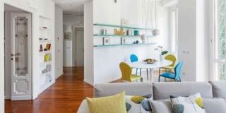 open space, divano grigio, cucina, zona pranzo, tavolo rotondo, sedie gialle e blu, portefinestre, porta in legno e vetro, ripiani, pavimento in parquet