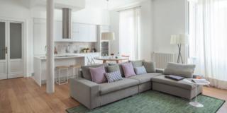 open space del bilocale moderno, divano con chaise longue in tessuto grigio, tappeto, portefinestre, pilastro, cucina, parquet