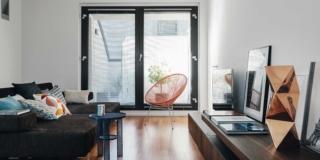 soggiorno al piano superiore, vetrata affacciata sul terrazzo, divano nero, tavolino, poltroncina elastica rossa, mobile modulare basso, pavimento in parquet di teak