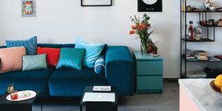soggiorno del piccolo bilocale, divano con braccioli larghi in finitura ottanio, cuscini tinta unita, coffee table, tappeto berbero, libreria in ferro a ripiani