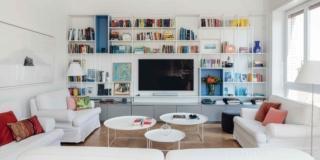 soggiorno dell'appartamento in centro, libreria a giorno bianca con zona tv, divani in tessuto bianco, tavolini rotondi, cuscini rossi, portafinestra, parquet in rovere, lampada da terra