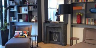 Parete soggiorno arredata con chaise-longue e con libreria, specchio e finto camino in ghisa, tutti dipinti grigio antracite