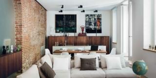 soggiorno dell'abitazione ecocompatibile, arco in mattoni, vetrata satinata, divani bianchi, mobile madia in legno su disegno, finestre, portafinestra