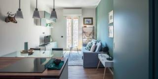 soggiorno del trilocale, portafinestra, parete azzurra, divano, tappeto, mobile tv, blocco cucina, tre lampade a sospensione, porta scorrevole, controsoffitto
