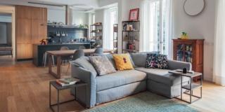 open space dell'appartamento anni '50, zona conversazione, divano grigio con chaise-longue, libreria vetrata, portafinestra, tappeto verde, pavimento in parquet, zona pranzo, tavolini