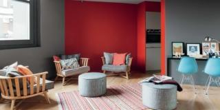 soggiorno del loft su due quote, poltroncine in legno, pouf rotondi, tappeto rigato, consolle, sedie azzurre, parete rossa, ingresso della cucina