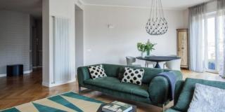 living, divano in velluto, radiatore a parete, lampada a sospensione di design, portafinestra, tappeto a losanghe, cuscini, zona pranzo