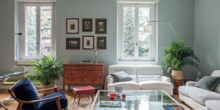 soggiorno della casa classica, divani bianchi, pareti verde salvia, coffee table con piano in vetro, finestre, madia classica, poltroncina di modernariato, lampada da terra orientabile, sgabello rosso, tappeto, piante in vaso, stampe incorniciate