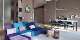 soggiorno, pareti grigio tortora, porta vetrata, divano destrutturato azzurro e viola, cuscini, tavolini a forma di tronco, tavolo da pranzo con piano in vetro, libreria a colonna, ripiani, tappeto grigio