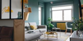 soggiorno del bilocale rinnovato, pareti color ottanio, divano grigio con chaise-longue, tavolini rotondi, passatoia, portafinestra, finestra, radiatore giallo, sedia, piante verdi, mensola a zig zag sospesa, lampadario