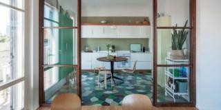 Una vetrata tra cucina e soggiorno nella casa con rivestimenti d'effetto