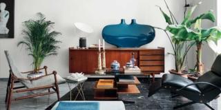 soggiorno del bilocale, zona conversazione, poltrona in pelle, coffee table con piano in vetro, chaise-longue, madia, vaso in vetro soffiato azzurro, lampada da tavolo di design, piante in vaso, pavimento in marmo a due colori, sospensione di design