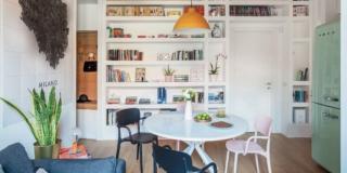 soggiorno del trilocale, libreria in cartongesso, tavolo rotondo bianco, sedie in materiale plastico, soffitto giallo, scultura a parete, frigo verde acqua anni '50, porta d'ingresso, pavimento in parquet, lampada a sospensione gialla