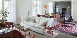 soggiorno open space del trilocale, divano in tessuto bianco, panchetta, tavolino tondo rosso, portefinestre, tappeto, poltrona, travi a vista, tavolo da pranzo