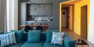 soggiorno del bilocale, cucina a vista grigio antracite, ingresso giallo, portafinestra, tendaggi, tavolo da pranzo, divano color petrolio, cuscini fantasia, pavimento in parquet, sospensione di design, tavolino